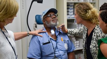 A pathologist and graduate students examine a Veteran's throat to explore his communication abilities