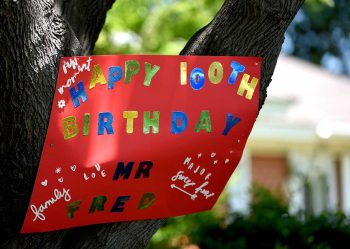 A sign in a tree celebrates the centenarian's birthday