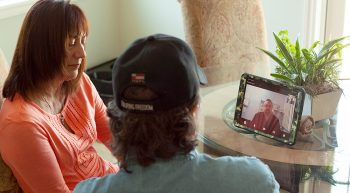 Two people talk to a health care provider using telehealth