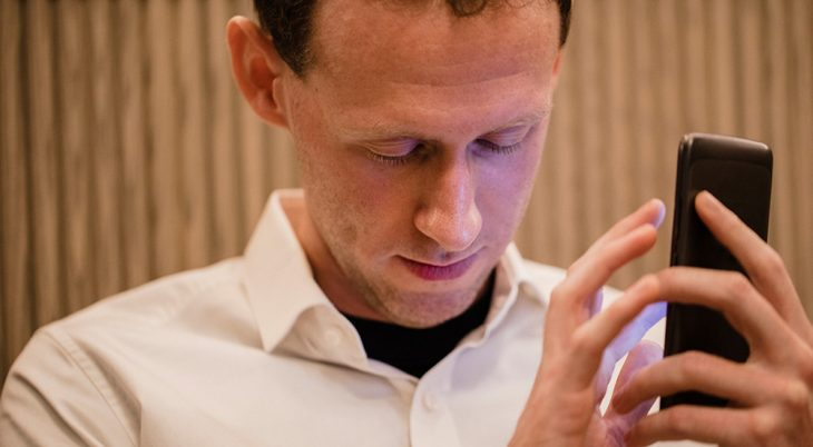 A close-up of a man wearing casual clothing, he has his smartphone in his hand and he is using a visually impaired mobile app to help assist him.
