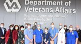 Large group of nurses stand in front of a VA sign