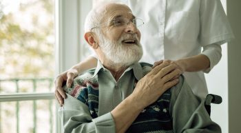 Senior man sitting on the wheelchair, laughing and holding his hospice nurse's hand
