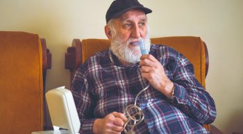 Elderly patient using an oxygen inhaler to assist his lung function