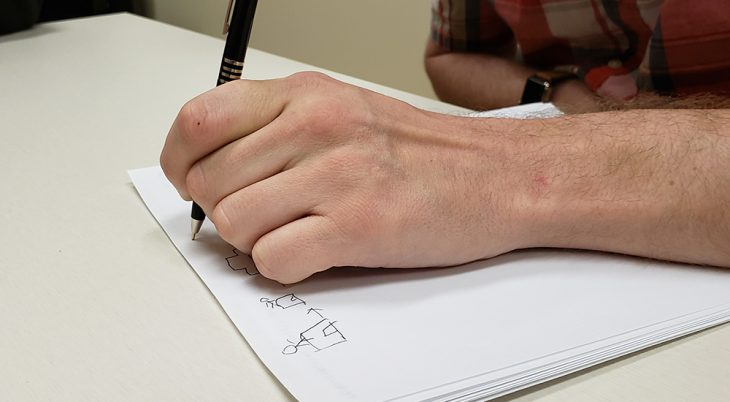 A man's hand drawing small pictures