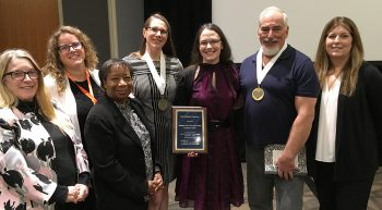 A man and six women pose with an award