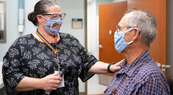 Woman wearing special mask talks to patient wearing mask