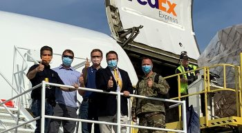 Five men give thumbs up on airplane loading lift