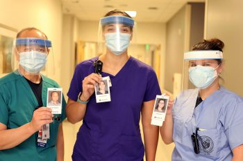 Three nurses, each wearing a mask for safety, hold up photo badges