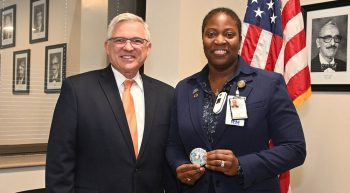 woman nurse receives award from man in suit