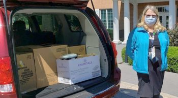 Woman standing next to car loaded with boxes