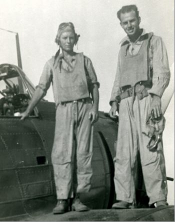 Paul Hilliard, left, stands on an SDB Dauntless dive bomber with another crew member.