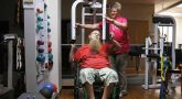Woman assisting man in wheelchair on exercise machine