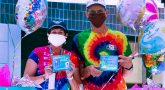 Man and woman in tie-dyed t-shirts hold up baby shower gifts
