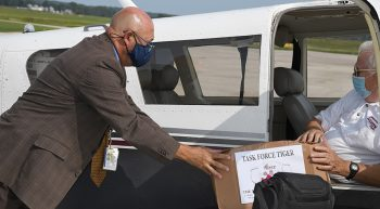Interim Medical Center Director Paul Hopkins accepts the first box of masks.