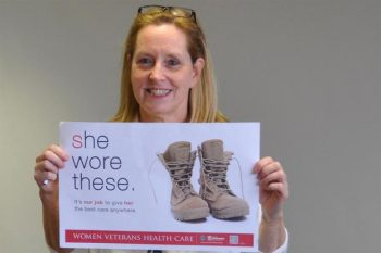 woman veteran holding va health care sign