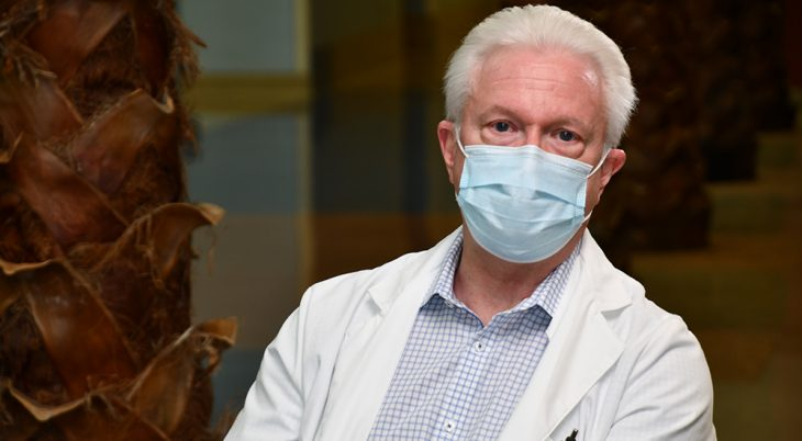 Male doctor in white coat wearing mask