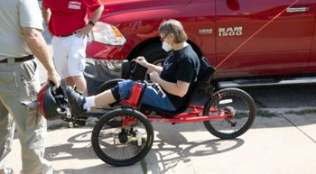 Woman adjusts handlebars on recumbent bicycle
