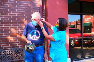 A clinician fits a Veteran with a hearing aid