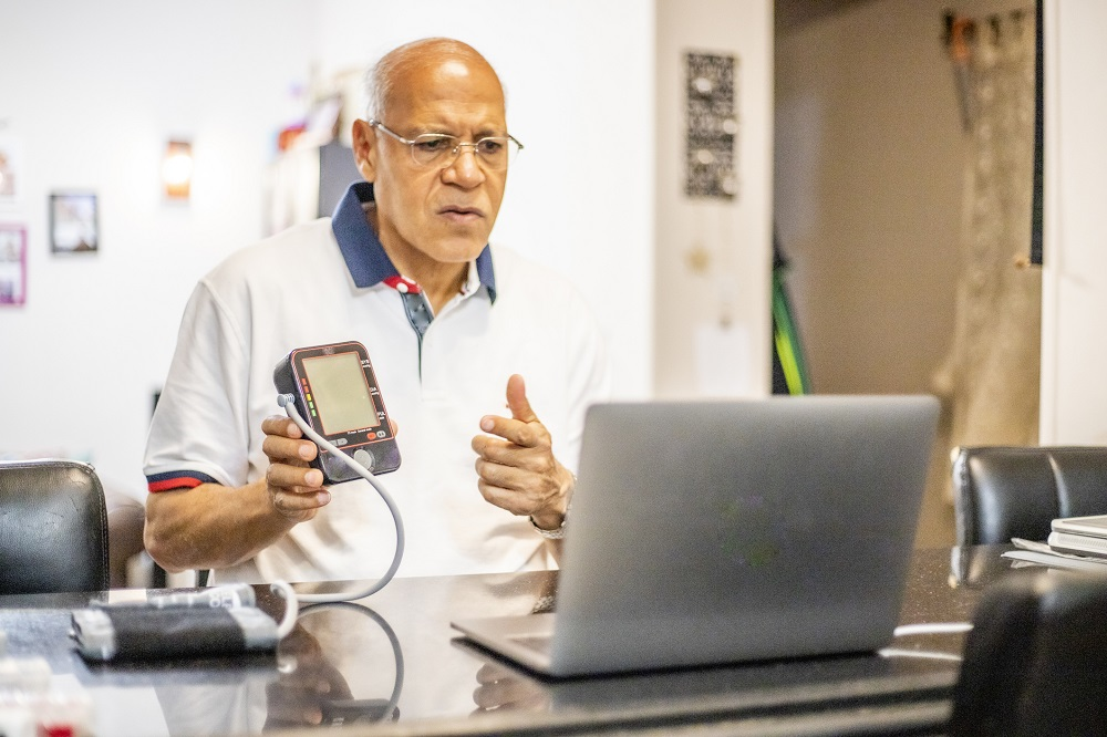 Man holding medical monitoring device in telehealth session