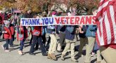 People carrying Thank You Veterans banner in parade