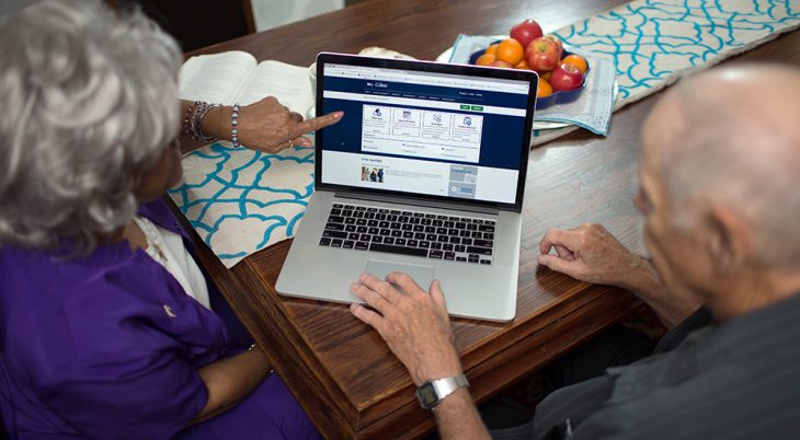 Man and woman reading information on laptop
