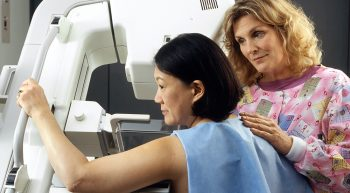 Nurse assisting women with mammogram