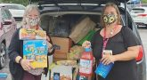 Two women in masks with donated food items