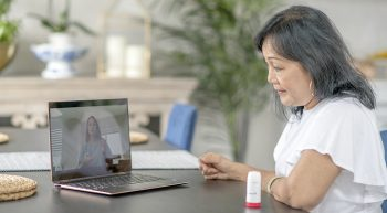 A senior woman sits in her home and discusses with a medical professional via video call on her laptop.