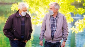 Two men walking and talking near wooded area
