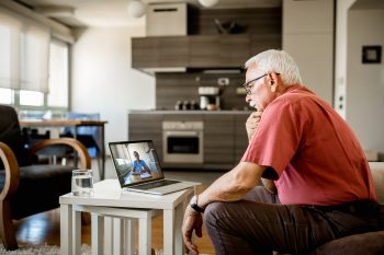 Senior man on online therapy. He is sitting on the sofa in a living room, having a video call with a doctor