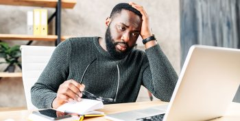 Frustrated sad black guy is watching at laptop screen and holding head with his hand. He read bad news.