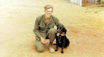 Young American Soldier in Vietnam posing with a black Labrador dog