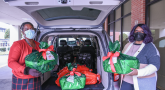 Two women load presents in an SUV