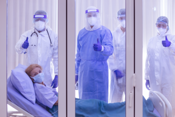 Four doctors in PPE and patient in bed