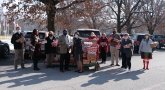 Ten people holding presents in a parking lot