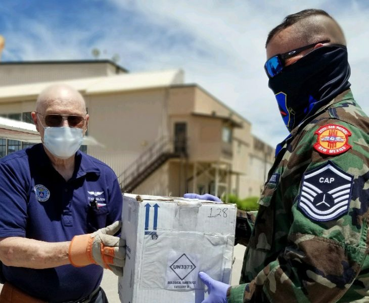 Maj. Stanley Nelson (left) of the Roswell Composite Squadron hands a package of COVID-19 test samples to Master Sgt. Jeffrey Barlow of the Falcon Composite Squadron at Albuquerque International Sunport. Photo by Lt. Col. Beverly Vito, Albuquerque Heights Composite Squadron.
