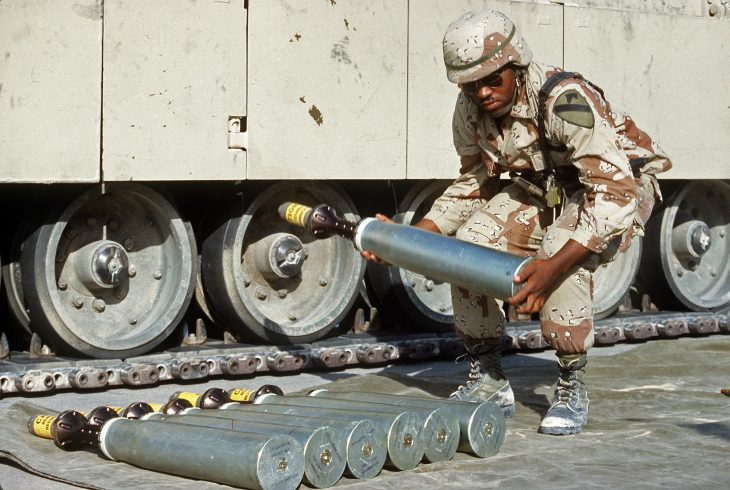 An ammunition specialist carries a 105mm armor-piercing, discarding sabot round, to be used in an M-1 Abrams main battle tank, during Operation Desert Shield.