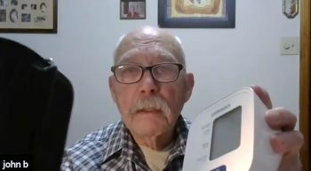 Elderly man holding blood pressure monitor