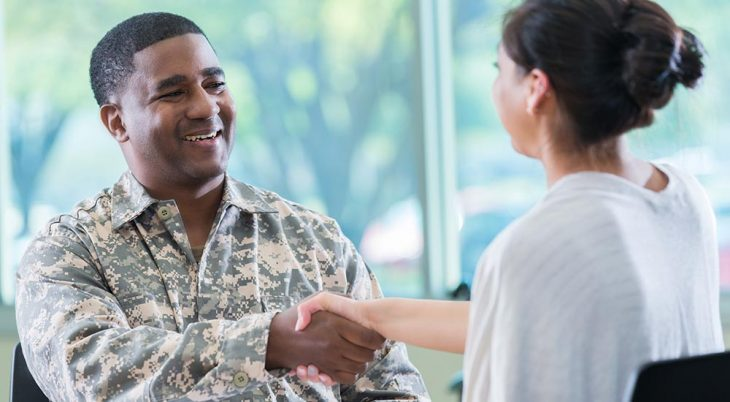 Soldier in fatigues shaking hands with woman
